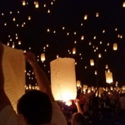 crowd releasing lanterns into night sky
